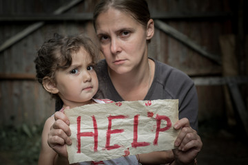 "A woman with a child holding a sheet of paper. On a sheet of paper the word ""help""."