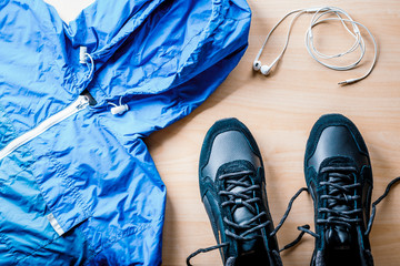 Sports equipment - running shoes . Sports background on a wooden floor , overhead view.