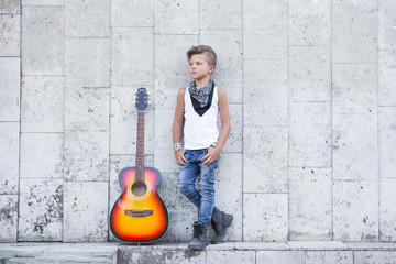 A little Boy stands next to a guitar and put his hands in his pocket . He looks to the side . Standing against the wall .