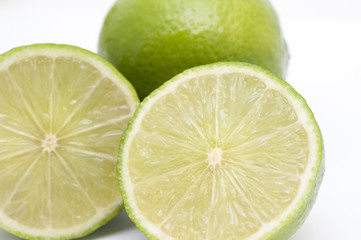 Close-up of two fresh nutritious limes, on white