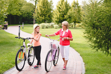 Happy active senior woman walking with bicycles with her grandaughter in park at summer