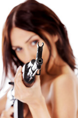 Sexy nude brunette girl model with weapon.