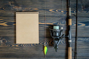 Fishing tackle with a bait for a predator on a wooden dark background a table and a notebook with the place for the text