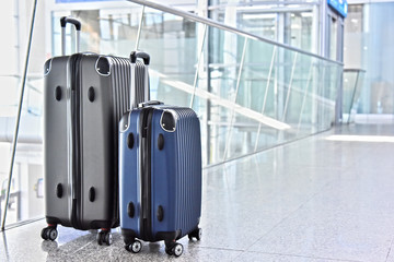 Two plastic travel suitcases in the airport hall