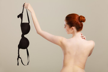 Naked woman holds black bra in hand