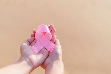Healthcare and medicine concept - womans hands holding pink brea