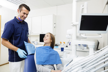 Happy Patient Looking At Dentist In Clinic