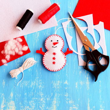 Cute felt Christmas snowman ornament, scissors, thread, needle, cord, felt sheets and scraps on wooden background. Supplies for making handmade snowman. Christmas kids crafts idea. Top view