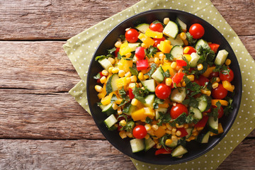 Dietary salad of corn, tomatoes, cucumbers and pepper. horizontal top view