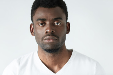 Highly-detailed close up portrait of good-looking young dark-skinned man wearing casual white T-shirt, looking at camera with serious and thoughtful expression on his face. Human emotions and feelings