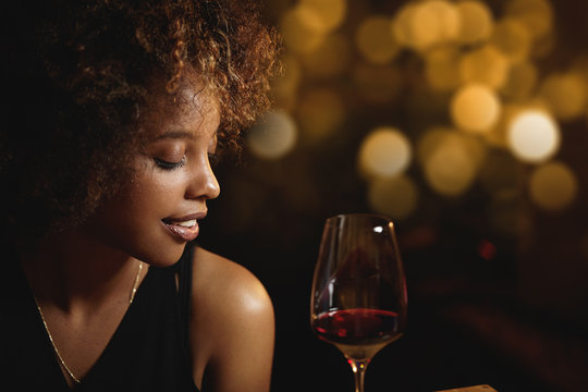 Profile of dark-skinned luxurious woman with Afro haircut wearing elegant evening dress drinking red wine, sitting at restaurant against blurred background for your text or advertising content