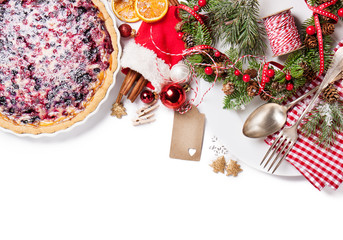 Christmas food concept - wild berry pie with plate, fork and spoon with christmas decoration, top view, isolated empty space