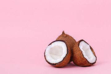 Coconut on pink background. Minimal style. Two halves of coconut