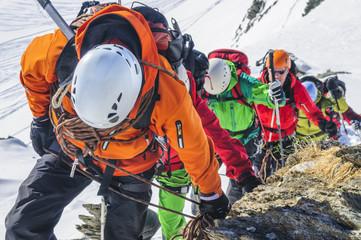 Bergführer führt eine Gruppe beim Aufstieg