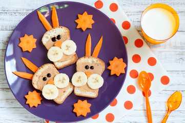 Breakfast for children with sandwiches and milk. Funny rabbit face sandwiches with peanut butter, banana and carrots