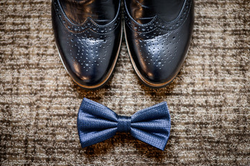 Beautiful stylish man's shoe and tie bow