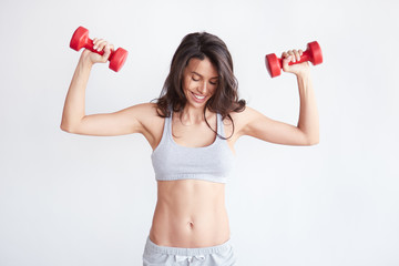 Athletic woman with dumbbells on white background