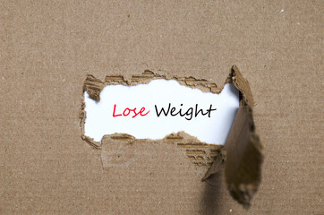 The word lose weight appearing behind torn paper