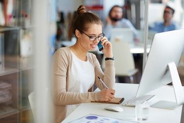 Young professional businesswoman working in public relations talking on phone with partners making notes in small notebook, sitting at computer desk in modern office space
