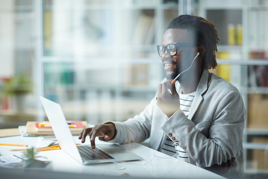 Young charismatic African-American businessman sitting at desk in modern office laughing as he is talking to someone using headset and making notes in laptop computer, behind glass wall shot