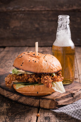 Fresh and tasty hamburger with a beer on a wooden table.