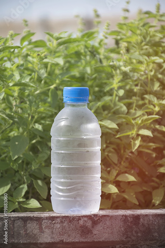 water bottle on concrete floor with nature background