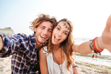Couple taking selfie and laughing on the beach