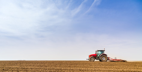 Farmer in tractor preparing land with seedbed cultivator Wall mural