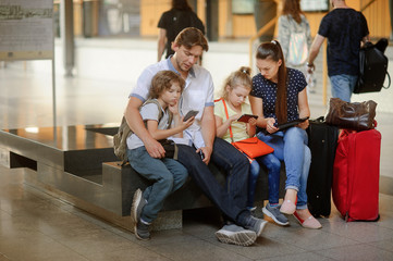 Young parents with two children at the railway station.