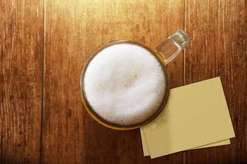 Glass of Beer on the Wooden Table at Bar with Blank Paper Note