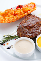 Succulent thick juicy portions of grilled fillet steak served with puree and sauces on a white plate
