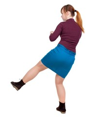 skinny woman funny fights waving his arms and legs. red-haired girl in a blue skirt leg beats.