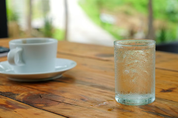 White coffee and glass water on wooden table.blurred green backg