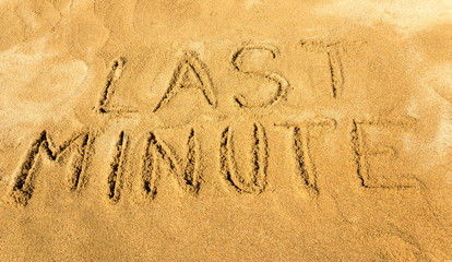 Words last minute handwritten on the sandy beach