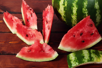 Wall Mural - Bright red slices of watermelon on a wooden table with boards.
