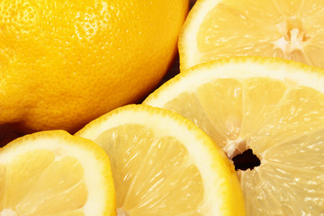 Wall Mural - bright yellow lemon slices on wooden background close-up.