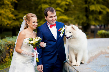 Happy wedding couple with cute white hasky
