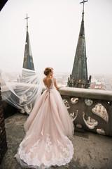 Happy bride in amazing dress on old balcony