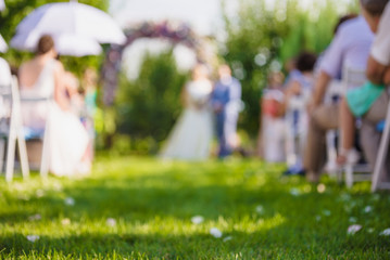 Wedding decorations, groom and bride, guests in the garden. Blurred