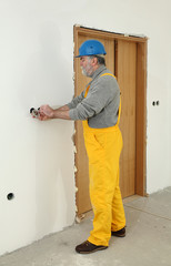 Electrician at construction site install electrical plug to wall