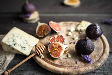 Fresh figs with honey and blue cheese on rustic wooden background