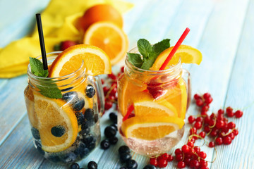 Refreshing water with fruits on table