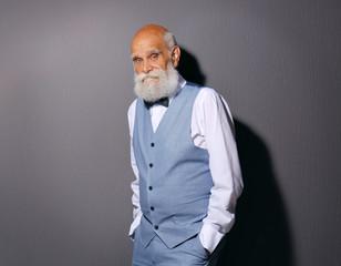 Elderly bearded man in stylish suit on grey background
