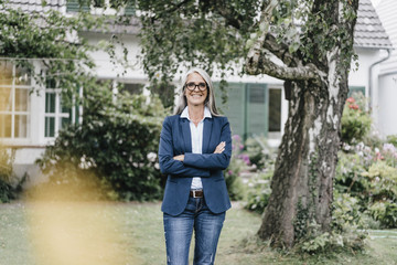 Portrait of smiling businesswoman with long grey hair wearing spectacles standing in the garden