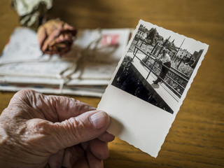 Old woman holding picture of her boyhood friend in hand, old letters and dried rose