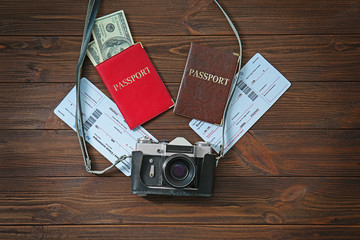 Vintage camera with passports and cash on wooden background