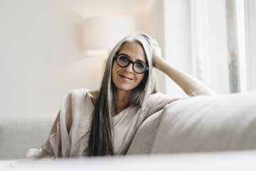 Portrait of smiling woman with long grey hair sitting on the couch