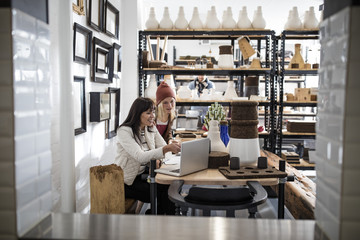 Two women with laptop in shop with shelf in background