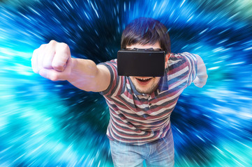 Happy young man is playing racing videogame in 3D virtual reality simulator using headset. Flying in virtual reality.