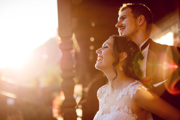Happy bride and groom enjoing the view from balcony during sunse